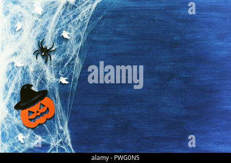 Halloween background. Spider web, spiders and smiling jack decorations - the symbols of Halloween on the dark blue wooden background - Stock Photo