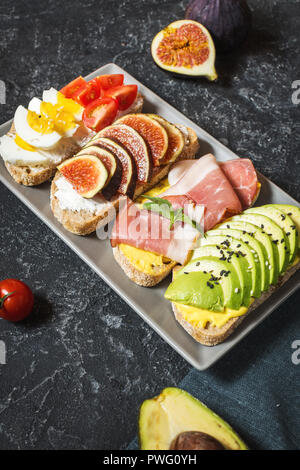 A set of avocado sandwiches, cherry tomatoes and eggs, figs, prochutto on a stone background. - Stock Photo