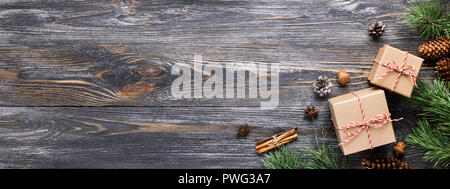 Christmas gifts in rustic style. Two gift boxes with cinnamon sticks, pine cones, anise stars and pine branches on wooden table. Top view, banner for website. - Stock Photo