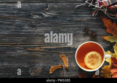 Autumn hot tea with lemon decorated yellow and red leaves, and checkered scarf on wooden table. Top view with copy space. - Stock Photo