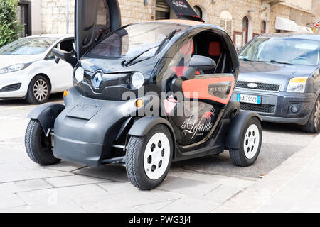 Close-up of a Renault TWIZY electric  two-seat vehicle car. Alghero, Sardinia, Italy - Stock Photo