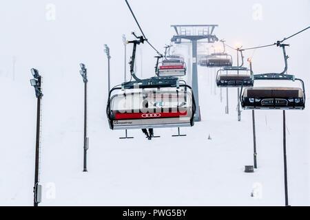 Ruka, Finland - November 24, 2012: Skiers are sitting on the chair ski lift at Ruka ski resort in freezing day. - Stock Photo