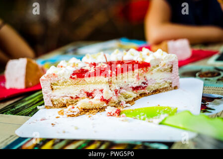 Cutting children birthday cake at kid birthday celebration. Layered cake with ice cream and strawberry is cut at birthday party event with children de - Stock Photo