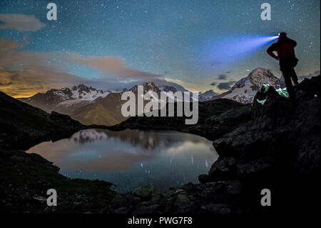 Hiker on top of rocks admiring the stars reflected in Lacs De Cheserys with Mont Blanc massif in the background, Chamonix, Haute Savoie, France - Stock Photo