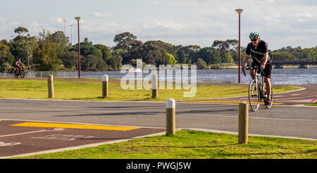 Caucasian male riding bicycle cycling along Swan River Perth Western Australia. - Stock Photo