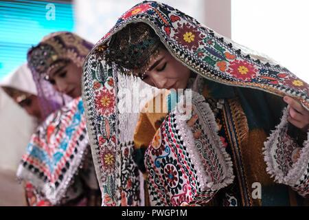 Young Uzbek woman wearing traditional kokoshnik tillya-kosh or tilla kosh forehead decoration with a lot of pendants and silk embroidered costume in Samarkand region Uzbekistan - Stock Photo