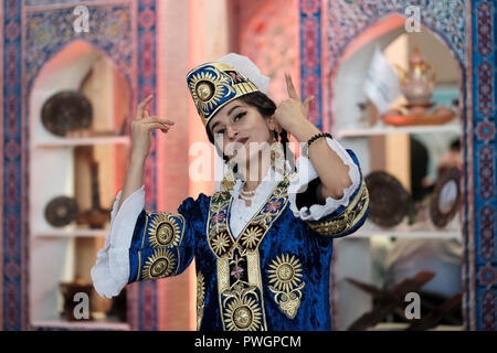 Young Uzbek woman wearing traditional garment at the 24th Tashkent International Tourism Fair (TITF) in the city of Tashkent capital of Uzbekistan - Stock Photo