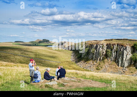 11 August 2018:  Hadrian's Wall, Northumberland, UK - Group of gray haired seniors sitting on the grass at Walltown Crags. - Stock Photo