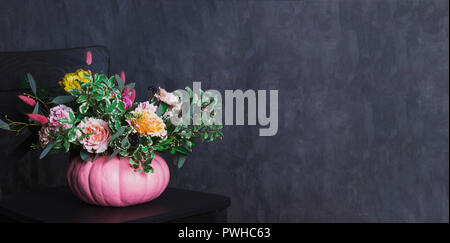 Autumn floral bouquet in colored pumpkin vase on black chair, banner - Stock Photo