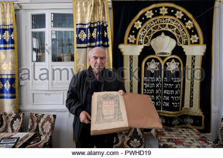 Abram Iskhakov the president of the Bukhara Jewish Community holds a 18th century Talmud which is a central text of Rabbinic Judaism inside the old Bukhara Jewish synagogue which dates to the 16th-century in the city of Bukhara known as Bokhara in 19th and early 20th century in Uzbekistan. Emigration to Israel and the west has left a fast-dwindling Jewish community in Bukhara, and only about 500 Jews remain in the city - Stock Photo