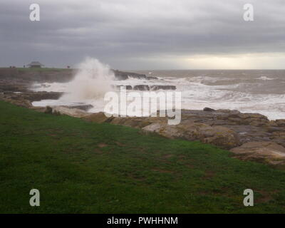 Porthcawl on a stormy day with waves crashing onto rocks, South Wales - Stock Photo