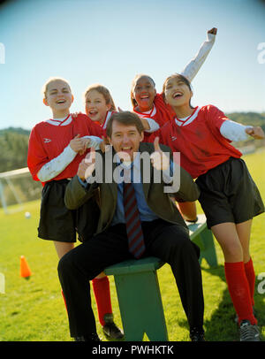 Soccer team and coach pose for a photo. - Stock Photo