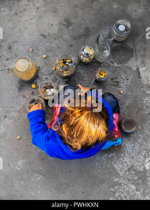 Child playing with mud and jars - Stock Photo