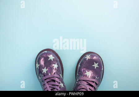 Cute child's purplecolor shoes on blue background with copyspace. - Stock Photo