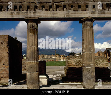Italy. Pompeii. Roman city destroyed in 79 AD because of the eruption of the Vesuvius volcano. In the foregorund, Portico of the Samnite period. At the background, remains of the Doric columns of the Temple of Jupiter (Fortuna Augusta) at the Forum. La Campania. - Stock Photo