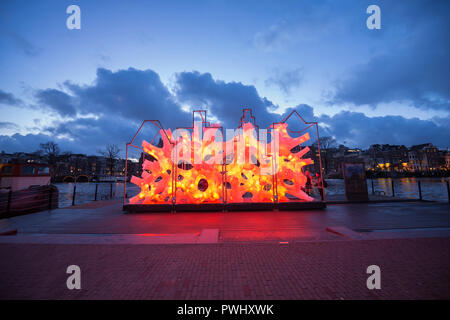 Amsterdam during Amsterdam Light Festival with color changing artwork 'Rhizome House'in red orange of 'DP Architects' with beautiful sky, river Amstel - Stock Photo