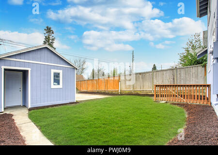 Large fully fenced back yard with green grass and one car detached garage. - Stock Photo