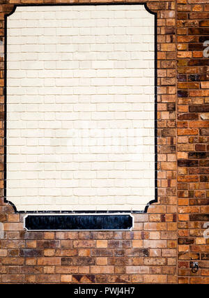 Blank white painted  adverting space surrounded with black boarder on brick wall, with blank black street name plate underneath. - Stock Photo