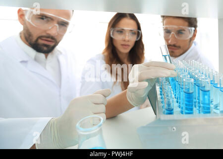 background image is a group of scientists studying the liquid in the glass tube. - Stock Photo