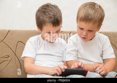 Two little boys in white T-shirts are sitting on the sofa at home. One boy shows something to another on smartphone. - Stock Photo