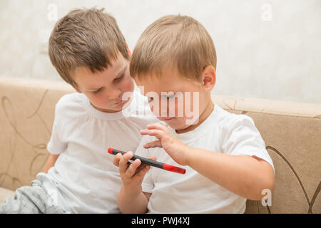 Two little boys in white T-shirts are sitting on sofa at home. One boy plays games on smartphone,  second one looks - Stock Photo
