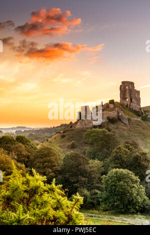 After another cold night, a colourful sunrise over the historic ruins of Corfe Castle heralds the start to rising temperatures in the county of Dorset - Stock Photo