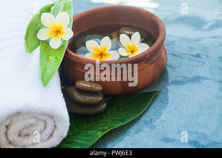 White towel, Yellow flowers, green leaves and cosmetics on blue marble background - Stock Photo