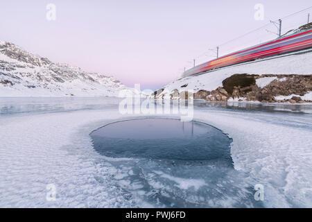 The Bernina Express train runs beside the frozen Lago Bianco Bernina Pass canton of Graubünden Engadine Switzerland Europe - Stock Photo