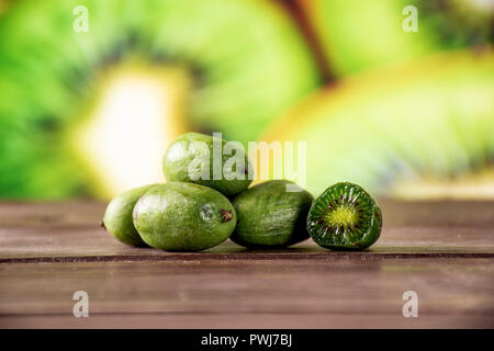Group of five whole one half of fresh green mini baby kiwi fruit with sliced kiwifruit in background - Stock Photo