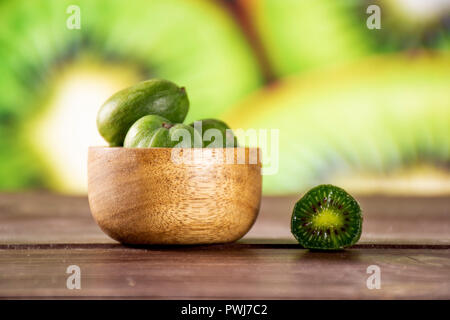 Lot of whole one half of fresh green mini baby kiwi fruit with wooden bowl with sliced kiwifruit in background - Stock Photo