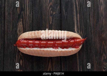 hot dog with smoked sausage on dark wooden background.photo with - Stock Photo