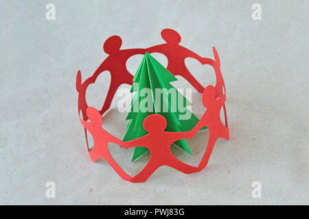 Red paper people in a circle around a tree on recycled paper background - Ecology concept - Stock Photo