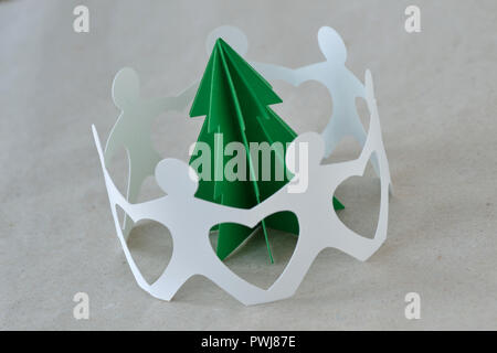 White paper people in a circle around a tree on recycled paper background - Ecology concept - Stock Photo