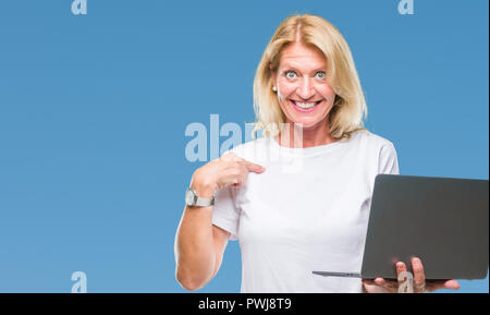 Middle age blonde woman using computer laptop over isolated background with surprise face pointing finger to himself - Stock Photo