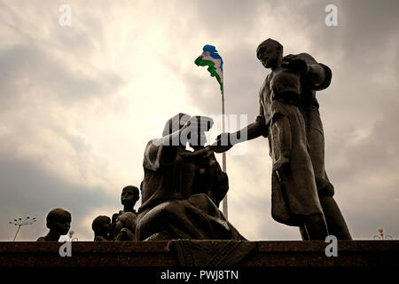 The Uzbek national flag flutters over a Soviet-era monument (created by sculptor Dmitry Ryabichev in 1982) to the blacksmith Shaakhmed Shamakhmudov and his wife Bahri Akramova who adopted 15 children of different nationalities, who lost their parents and were evacuated to Tashkent during WWII placed at the Park of Amity in Tashkent, capital of Uzbekistan. During Second World War more than one million evacuees, including more than 200,000 children who had lost their parents, were moved to Uzbekistan. Every day, between 200 and 400 orphans arrived at Tashkent railway station. - Stock Photo