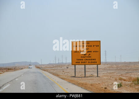 Warning sign in Hebrew, Arabic and English Caution! Tanks crossing and dust clouds. Photographed in The Negev Desert, Israel on the way to Eilat - Stock Photo