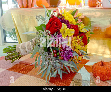 Photo of a colorful wedding bouquet with red roses, yellow alstroemeria, eucalyptus, daisies. - Stock Photo