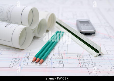 Rolled-up architectural plans and drawing utensils - Stock Photo