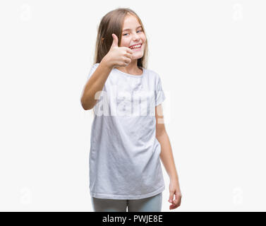 Young beautiful girl over isolated background doing happy thumbs up gesture with hand. Approving expression looking at the camera with showing success - Stock Photo