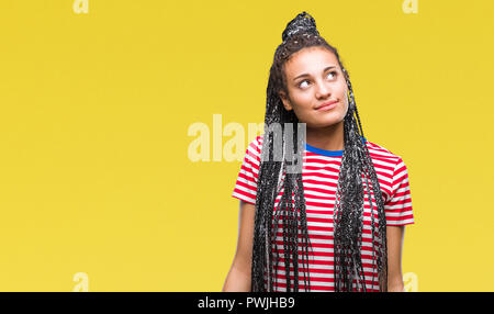 Young braided hair african american girl over isolated background smiling looking side and staring away thinking. - Stock Photo