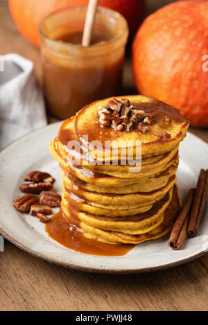 Pumpkin spice pancakes with caramel sauce and nuts on a plate, closeup view, selective focus. Autumn comfort food - Stock Photo