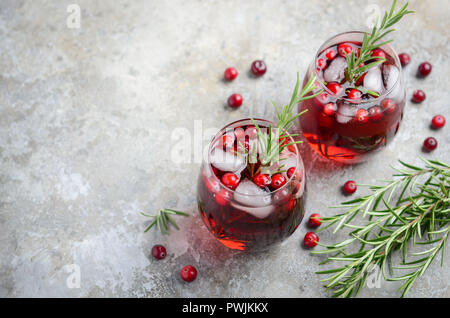Cold refreshing drink with cranberries and rosemary on a gray concrete background - Stock Photo