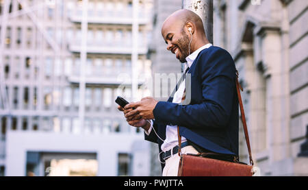 Happy young businessman with a smartphone walking outdoors in city street. African man in suit with earphones listening to music on a mobile phone out - Stock Photo