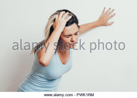 Woman suffering from dizziness with difficulty standing up while leaning on wall - Stock Photo