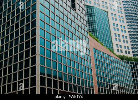Abstract glass exterior of modern office buildings in downtown Singapore with symmetrical patterns, reflections and perspective as abstract background - Stock Photo