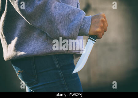 Concept on theme of attack: man in street with knife in his hands, close-up - Stock Photo
