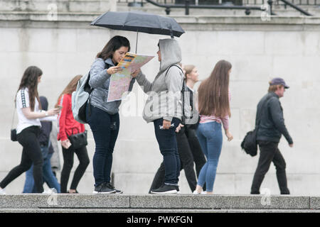 London UK. 17th October 2018. Pedestrians Shelter from the rain drizzle in Trafalgar Squre London on a wet ovecast day Credit: amer ghazzal/Alamy Live News Stock Photo