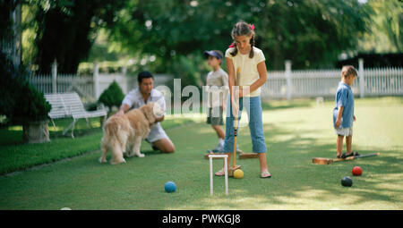 Girl playing croquet on a grassy lawn with her father and two younger brothers. - Stock Photo