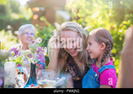 Summertime. a family of three generations gathered around a table in the garden to share a meal. Focus on complicity moment between a young mother and - Stock Photo