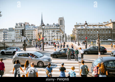 PARIS, FRANCE - September 01, 2018: Crowded street with cars and people with Notre-dame cathedral on the background - Stock Photo